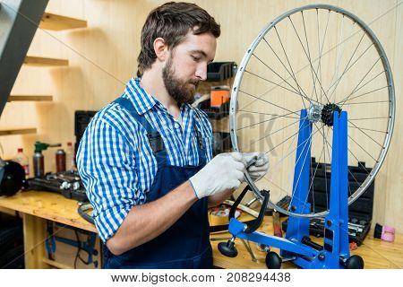 Repairman in gloves and uniform tightening hubs of bicycle wheel