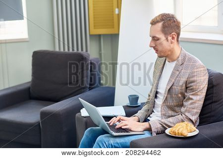Busy young man with laptop searching for job in the net while sitting at home