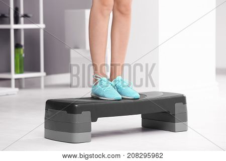 Young sporty woman training with stepper in gym
