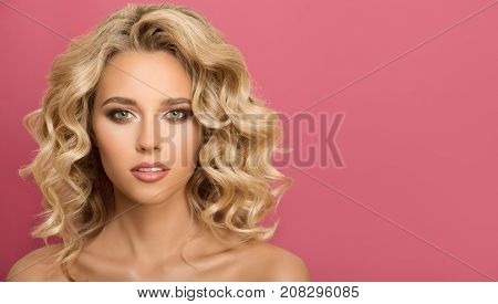Blonde woman with curly beautiful hair on pink background.