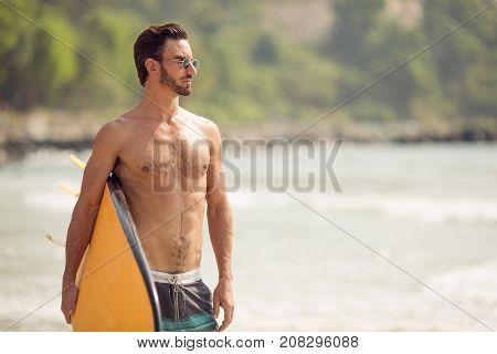 Surfer man with surfboard on sea coast.