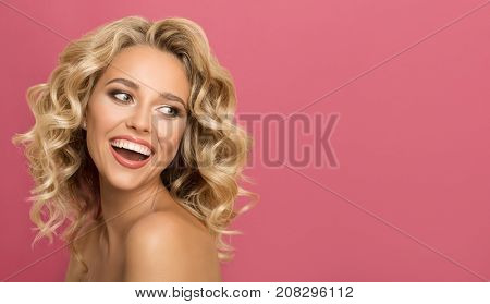 Blonde woman with curly beautiful hair smiling on pink background.