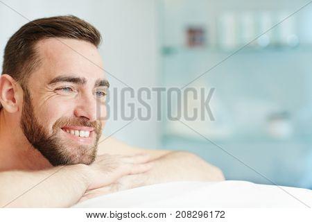 Smiling man enjoying anti-stress procedure while relaxing in spa salon