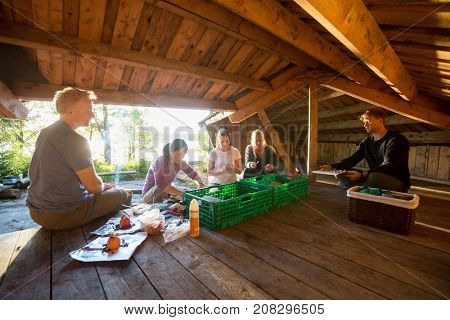 Multiethnic Friends Preparing Meal In Shed At Forest