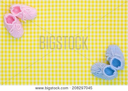 Kinitted Baby booties for a girl and a boy on a yellow gingham background.