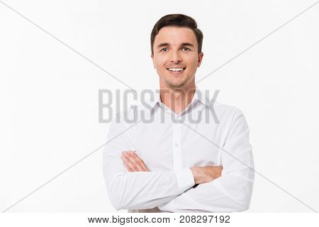 Close up portrait of a joyful young man in a white shirt standing with arms folded and looking at camera isolated over white background