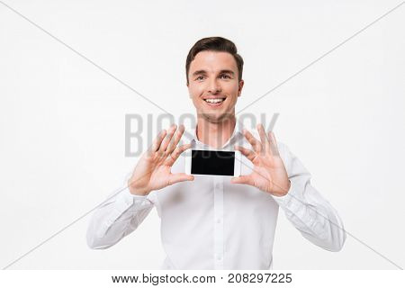 Portrait of a confident successful man in a white shirt showing blank screen mobile phone with two hands and looking at camera isolated over white background