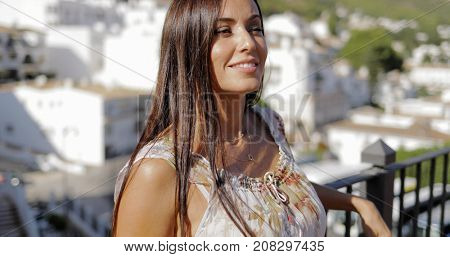 Elegant young woman in summer dress posing on city terrace looking relaxed and daydreaming happily on background of cityscape.