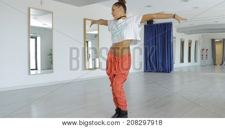 Young ethnic woman in sportive clothing practicing dance performance while posing alone in studio and training.