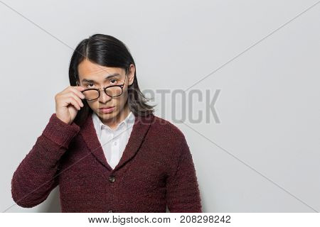 Strict young man taking off his eyeglasses while staring at camera