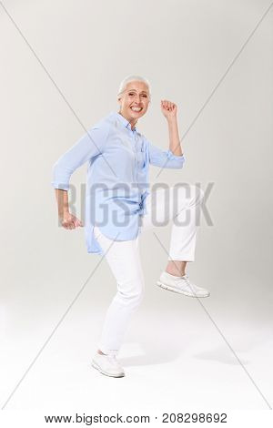Full-length photo of playful old lady, having fun over white background
