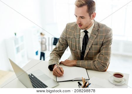 Busy young man writing in his notebook and reading online data in laptop