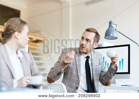 Businessman with cup of tea explaining his point of view to colleague in office at coffee-break