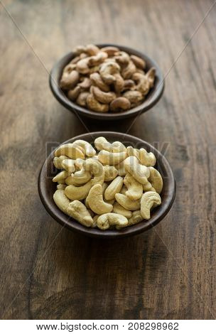 A healthy and nutritious cashew nut samples in wooden bowls. Cashew before and after processing.