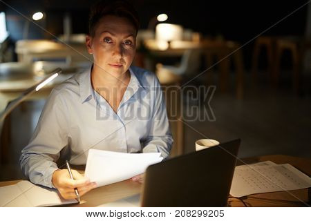 Middle-aged businesswoman with papers working overtime in office