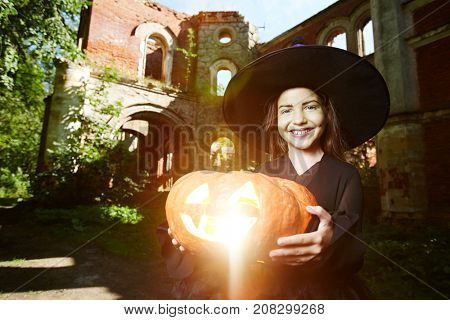 Happy girl in hat and black attire holding jack-o-lantern and looking at camera
