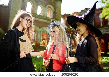 Friendly companions in witch attire interacting at halloween party on sunny day