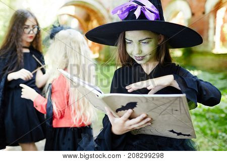 Evil girl in hat and witch attire keeping her hand over open spell-book during halloween magic