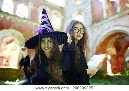 Two black halloween witches in black attire looking at camera