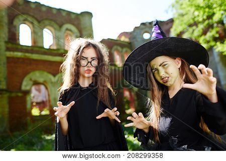 Two angry witches showing frightening hand gesture to you