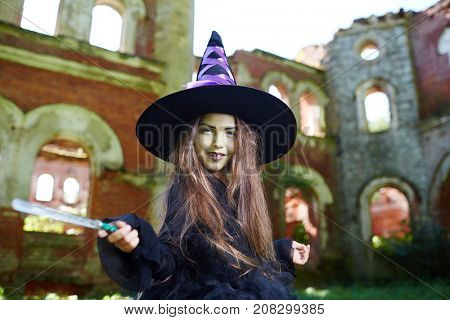 Cute little witch in halloween attire shaking by magic-wand