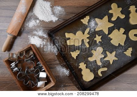Top view of a baking sheet with a holiday shaped sugar cookies, with a rolling pin and wood box of cookie cutters on the side.