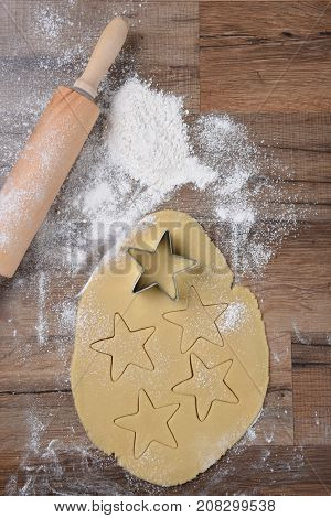 Top view of raw cookie dough with star shapes and cookie cutter on wood table with a rolling pin and flour sprinkles.