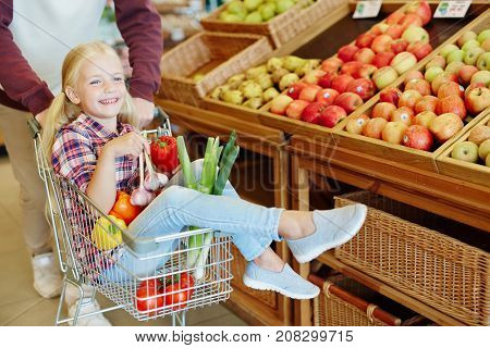Little girl sitting in shopping cart with vegs and enjoying cart ride