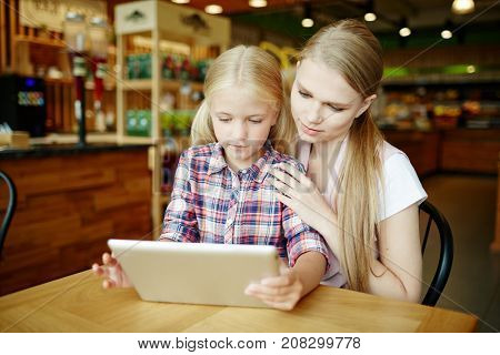 Young woman and her daughter choosing food from online menu in modern cafe at leisure
