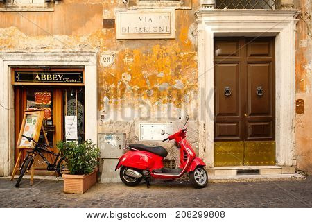 ROME.ITALY - JULY 21, 2017 : Typical street scene in Rome with a red scooter on an old narrow cobblestoned street