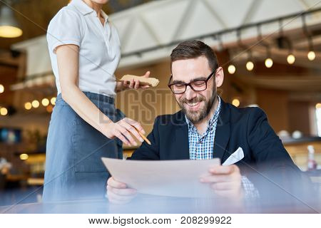 Modern businessman reading menu in cafe while waiter recommending him to order something special