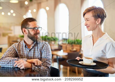 Friendly waitress bringing cup of tea or coffee on tray to one of guests of restaurant