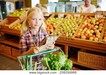 Little buyer with shopping list pushing cart with fresh vegetables