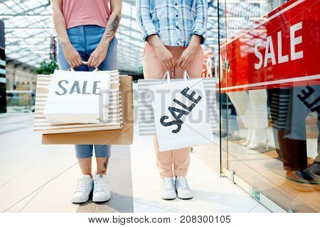 Two friends with paperbags made purchases in mall departments during seasonal sale