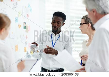Handsome African American police officer showing evidence taken from crime scene to his team while having discussion at modern open plan office