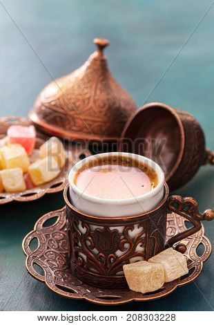 Traditional turkish coffee  and turkish delight on dark green wooden background.