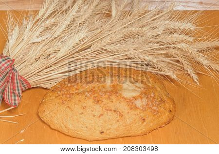 Loaf of Sliced French Bread with wheat sheaves on a cutting board