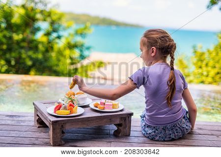 Adorable little girl enjoying eating sweets delivered by room service to swimming pool