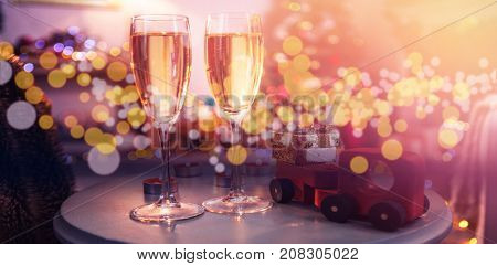 Champagne flutes with Christmas decorations on table at home