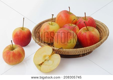 Group of small gala apple in basket over white background.