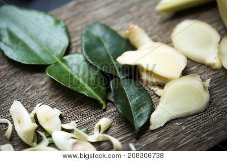 Closeup of fresh galangal lemongrass and kaffir leaves on wooden table