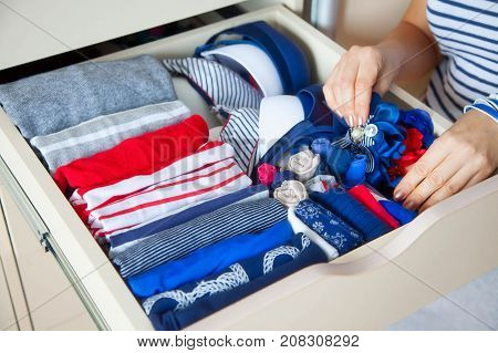 Neatly Folded Clothes With Accessories In Chest Of Drawers. Marine Clothing Style
