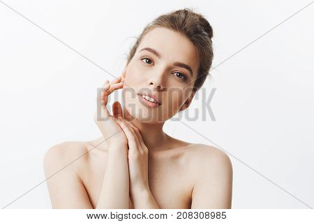 Beauty and health. Young good-looking skinny caucasian girl with dark hair in bun hairstyle being naked, looking in camera with relaxed and happy expression, touching hand with hands, feeling refreshed after spa treatments