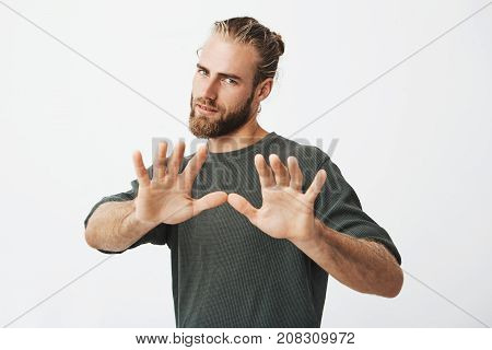 Handsome mature guy with beard holding hands in front of him with mean expression showing guy on street not to come closer to him