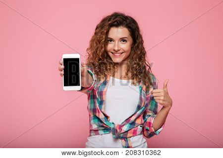 Young cheerful caucasian lady in casual clothes smiling and showing smartphone with blank screen isolated