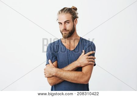 Close up portrait of attractive bearded man with good-looking hairstyle crossing hands on chest, looking at camera with flirty expression