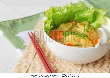 Homemade minced pork and shrimp wonton soup or dumpling soup in white bowl on wood table with copy space. Delicious dumpling soup for lunch or dinner. Wonton or dumpling soup is popular Chinese food. Dumpling soup ready to served.