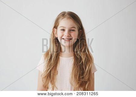 Close up of funny little girl with blue eyes and blonde hair laughing, looking in camera with satisfied expression, posing for family photo