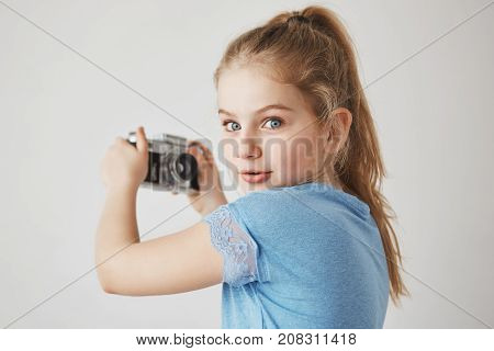 Close up portrait of cheerful cute girl with blonde hair and blue eyes, looking in camera with interested expression, going to take a selfie