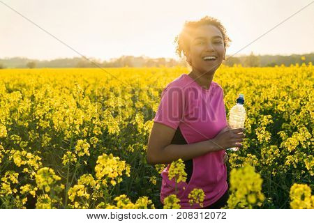 Outdoor portrait beautiful happy mixed race African American girl teenager female young woman athlete runner drinking water bottle in a field of yellow flowers at sunset in golden evening sunshine